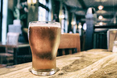 Closeup of a glass of fresh foamy beer on a table in a vintage b Stock Photos
