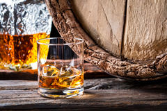 Closeup of glass of good cognac in the distillery basement. On wooden background royalty free stock photo