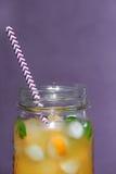 Closeup Glass jars of orange juice with ice and kumquat on viole Royalty Free Stock Image