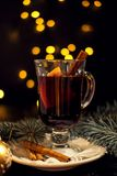 Closeup glass of mulled wine with orange and cinnamon on white plate, Christmas lights royalty free stock images