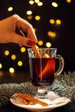 Closeup glass of mulled wine with orange and cinnamon in hand of woman on dark black background royalty free stock photo