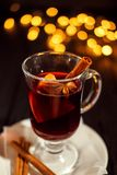Closeup glass of mulled wine with orange and cinnamon on white plate, Christmas lights stock photography