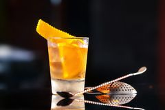 Closeup glass of old fashioned cocktail decorated with orange. At bar counter background royalty free stock image