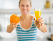 Closeup on glass of orange juice and orange in hand of woman Royalty Free Stock Images