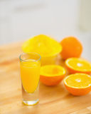 Closeup on glass of orange juice and oranges on cutting board Stock Photos
