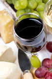 Closeup of glass of red wine, grapes and cheese, top view. Vertical Stock Photography