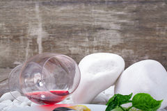 Closeup of a glass with red wine lying on white stones on a wooden background. Red alcoho drink. Closeup of a glass with red wine lying on the side on a white Stock Image