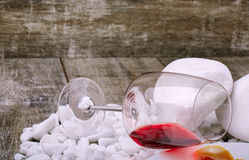 Closeup of a glass with red wine lying on white stones on a wooden background. Red alcoho drink. Closeup of a glass with red wine lying on the side on a white Royalty Free Stock Image