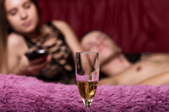 Closeup glass shompanskogo, young sexy couple in bed embracing and kissing Royalty Free Stock Images