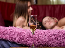 Closeup glass shompanskogo, young sexy couple in bed embracing and kissing Royalty Free Stock Photo