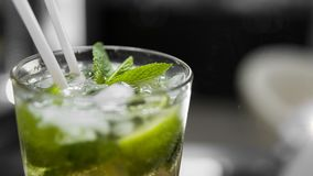 Closeup glass of unalcohol mohito cocktail with lime and mint and with a two tubes at bar background. Fresh drink for. Everybody. Freshy summer drink Stock Photo