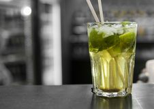 Closeup glass of unalcohol mohito cocktail with lime and mint and with a two tubes at bar background. Fresh drink for. Everybody. Freshy summer drink Royalty Free Stock Images