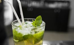 Closeup glass of unalcohol mohito cocktail with lime and mint and with a two tubes at bar background. Fresh drink for. Everybody. Freshy summer drink Royalty Free Stock Image