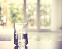 Closeup Glass of water on table in the living room , vintage and retro style Stock Images