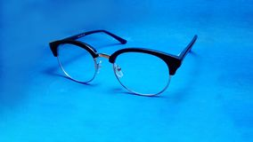 Closeup of glasses on blue background royalty free stock photo