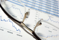 Closeup of glasses and financial report. Closeup on glasses and financial report with charts and data Stock Photo