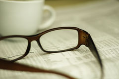 Closeup of glasses on a newspaper Stock Images