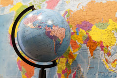 Closeup of a globe with asia and africa and a world map with nor. Th and south america on the wall in classroom stock photo