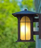 Closeup of a glowing lamp outside a wooden building in summer Royalty Free Stock Photography