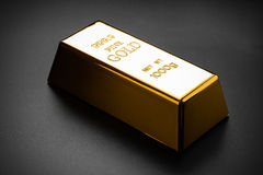 Closeup of gold bullion. On a dark background Stock Image