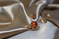 Closeup gold chain with pendant from gold and authentic baltic amber on light brown atlas. Gold earrings and ring with amber on background. small DoF focus put Royalty Free Stock Photo