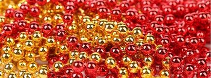 Closeup of gold and red beads. Stock Photos