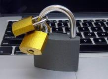 Padlocks on Laptop Keyboard - Data Protection Concept. Closeup of gold and silver padlocks on laptop keyboard stock photography