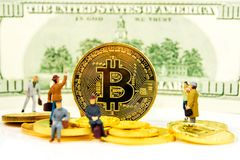 Crypto currencies, bitcoin especially is the possibility to get rich. Closeup of golden bitcoin coin on dollar banknote background with many golden coins at Royalty Free Stock Photo