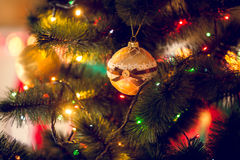 Closeup of golden Christmas ball hanging on decorated fir tree Royalty Free Stock Image