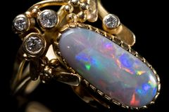 A golden ring with a colorful opal gemstone. Closeup of a golden ring with a colorful opal gemstone royalty free stock photography