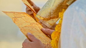 Closeup Golden Sheets with Vows in Newlyweds Hands stock video