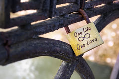 Closeup of golden wedding lock on iron rusty fence with One Love one Life text. Blurred background royalty free stock photography