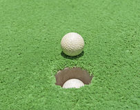 Closeup of golf ball by hole on green astroturf. Closeup detail of golf ball by hole on green artificial grass astroturf Stock Photos