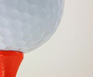 Closeup of Golf Ball on Tee. Macro of a White Golf Ball on an Orange Tee Stock Images