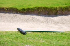 Closeup of a golf course sand trap and rake Stock Images