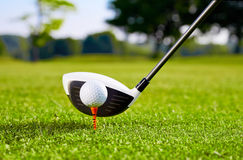 Closeup of golfball on tee for first stroke. On the green stock images