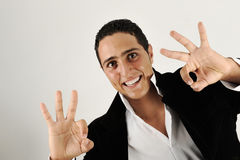 Closeup of good looking young man gesturing okay sign. Over white background Royalty Free Stock Photo