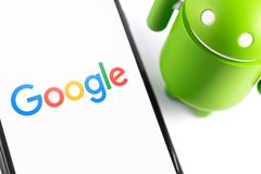 Closeup Google Android figure and smartphone. Google Android is the operating system for smartphones, tablet computers, e-books, game consoles, and other stock photos