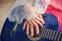 Closeup, gown, bride, two, white, newlywed, tender. Wedding couple hands with rings and veil on blue guitar Royalty Free Stock Photos