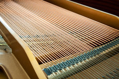 Closeup of grand piano showing the strings, pegs and sound board Stock Images