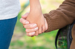 Closeup grandmother granddaughter holding hands. Outdoors environment Stock Images