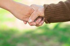 Closeup grandmother granddaughter holding hands Stock Photo