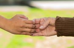 Closeup grandmother granddaughter holding hands Stock Image