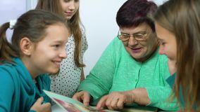 Closeup of grandmother showing old photo album to her granddaughters. Senior woman showing black and white photos to children. Family, relationship and stock video