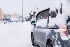 Closeup gray minibus dirty car covered with snow on city background. Side view. The concept snowy weather, snowfall, bad northern royalty free stock image