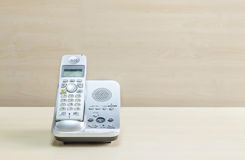 Closeup gray phone , office phone on blurred wooden desk and wall textured background in the meeting room under window light Royalty Free Stock Photography