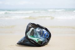 Garbage bag on the beach. Closeup of a gray plastic bag with collected garbage on the sand of a lonely beach,  next to the water, in the background royalty free stock photos
