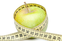Closeup of a green apple with a measuring tape Royalty Free Stock Image