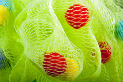 Closeup of Green Bath Puff with Red and Yellow Baubles Royalty Free Stock Photo