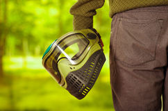 Closeup green and black protection facial mask held by man standing, forest background, paintball concept Royalty Free Stock Photos